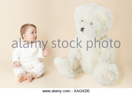 Studio portrait of baby girl next to giant teddy bear - Stock Photo