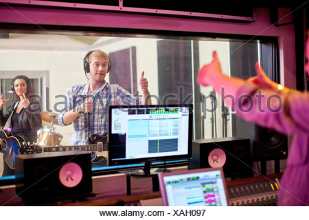 Young band recording in studio - Stock Photo
