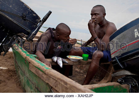 young fishermen sitting in a boat on the sand beach taking their breakfast after a night of work, Burundi, Nyanza Lac, Mvugo, Nyanza Lac - Stock Photo