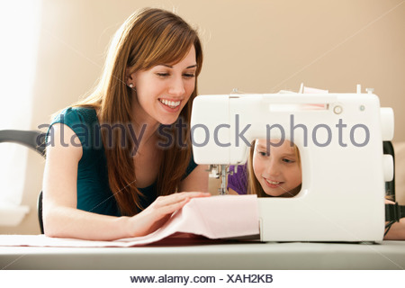 Girl (8-9) assisting young woman using sewing machine - Stock Photo