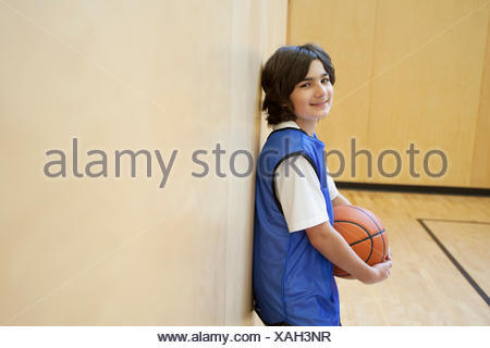 Male, middle school student posing with basketball. - Stock Photo