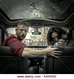 Couple in car with gun - Stock Photo