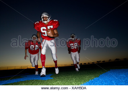 Three American football players, in red strips, running on pitch with ball at sunset surface level - Stock Photo
