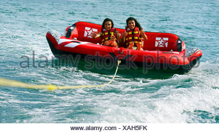 two girls are be pulled over the water with an air couch, France, Corsica - Stock Photo