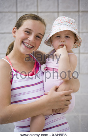 Girl holding baby - Stock Photo