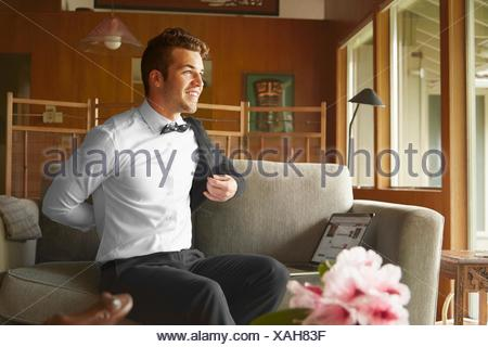 Man in smart clothes sitting on sofa putting on jacket - Stock Photo