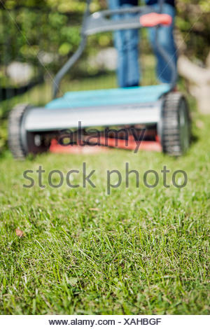Sweden, Sodermanland, Nacka, Teenage girl (16-17) mowing lawn with push mower - Stock Photo