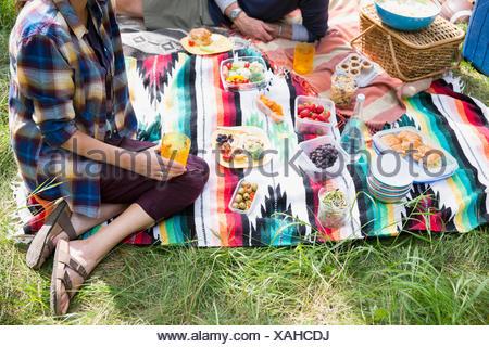 Couple enjoying picnic on blanket - Stock Photo