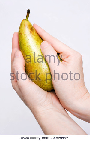 Hands holding a pear - Stock Photo