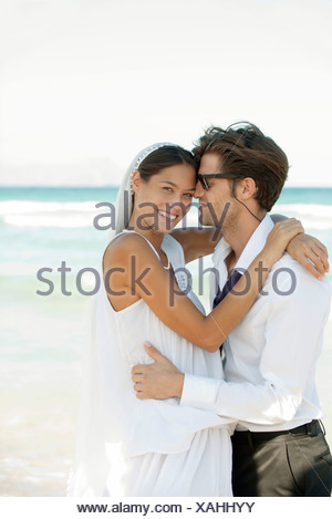 Bride and groom embracing a the beach - Stock Photo