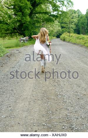 Rear view of young woman walking on rural road with flowers behind her back - Stock Photo