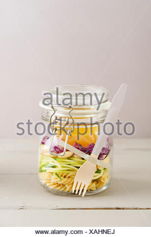 Vegan and vegetarian salad to go in a jar with pasta, spiralized zucchini, almonds, red cabbage and vinaigrette - Stock Photo