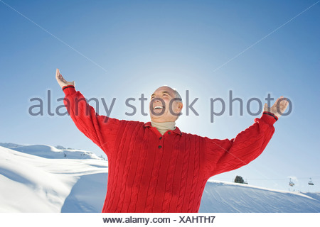 Italy, South Tyrol, Seiseralm, Senior man raising arms, smiling, portrait - Stock Photo