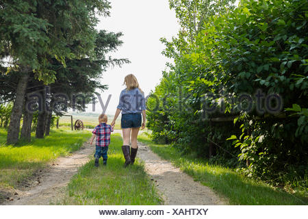 Mother and son walking on rural road - Stock Photo