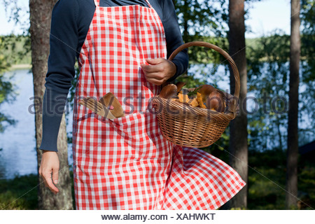 Woman with basket of mushrooms in forest - Stock Photo