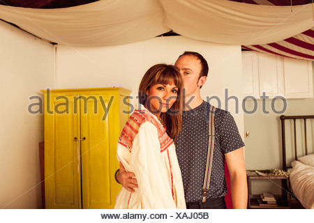 Man with arm around woman in bedroom - Stock Photo