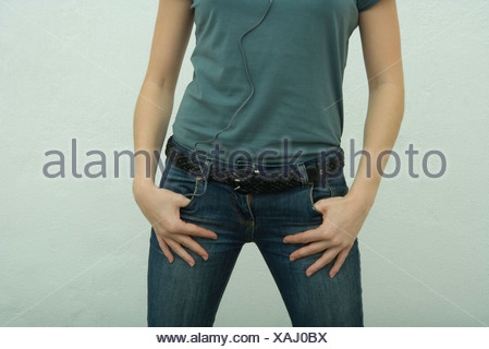 Female wearing jeans, hands in pockets, mid section - Stock Photo