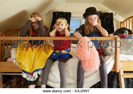 Three sisters, sitting on bed,  wearing fancy dress costumes, covering mouth, ears and eyes - Stock Photo