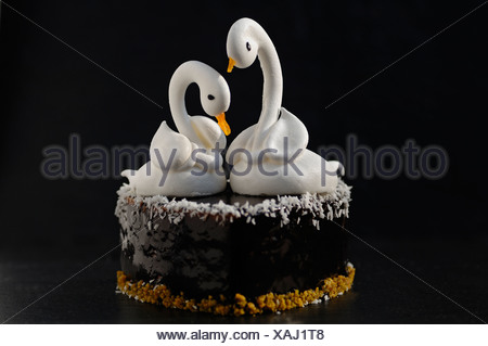 Two meringue swans on a chocolate heart, beaks made from apricots, on a slate in a patisserie - Stock Photo