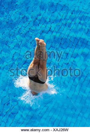 Male swimmer diving into pool, overhead view - Stock Photo