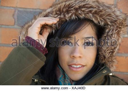 Close-up portrait of woman wearing fur hood - Stock Photo