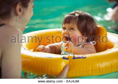 Baby girl using inner tube in swimming pool - Stock Photo