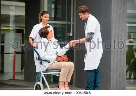 Male doctor shaking hands with a female patient sitting in a chair - Stock Photo