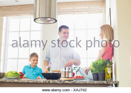 Family preparing food in kitchen - Stock Photo