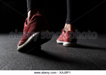 Close-up of Woman's legs in trainers at gym - Stock Photo
