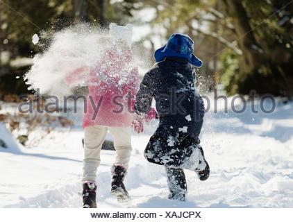 Two children running in snow - Stock Photo