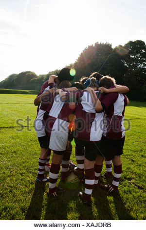 Teenage schoolboy rugby team in huddle - Stock Photo