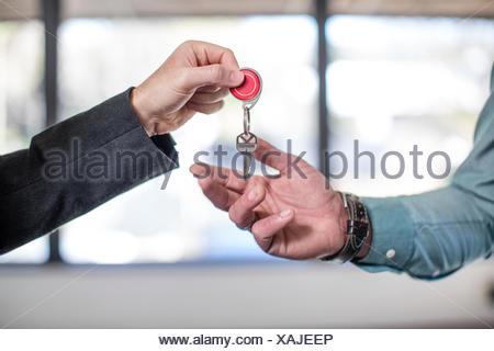 Estate agent handing keys to homebuyer, close-up - Stock Photo