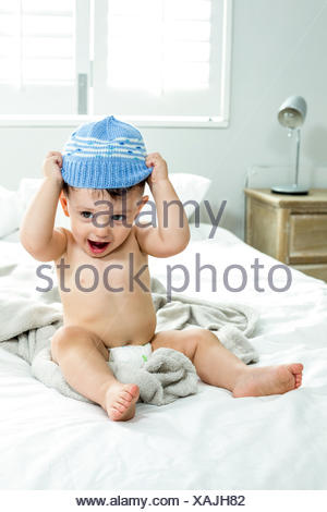 Cute baby boy wearing knit hat on bed - Stock Photo