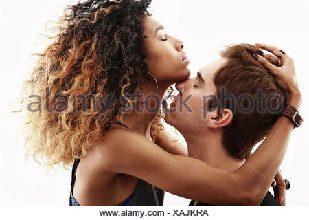 Studio portrait of passionate young couple embracing - Stock Photo