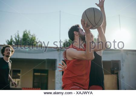 Friends on basketball court playing basketball game - Stock Photo