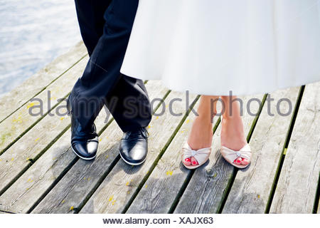 Sweden, Uppland, Arholma, Feet of man and woman standing on wooden pier - Stock Photo
