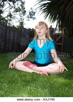 Female child blonde shoulder length hair, wearing a blue t shirt and black shorts, sitting in lotus yoga position on the lawn - Stock Photo