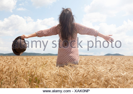 Mid adult woman standing in wheat field with arms out wide - Stock Photo