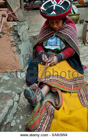 young woman in traditional dress working on a blanket at the local artisan workshop, Peru, Chincheros - Stock Photo