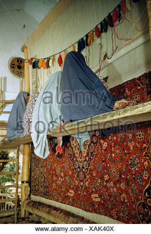 Cloaked women sit on a scaffold to make a rug in a home workshop. - Stock Photo