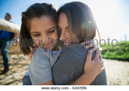 Close up mother and daughter hugging sunny playground - Stock Photo