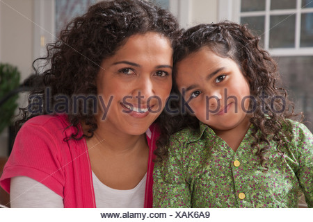 Hispanic woman smiling with her daughter - Stock Photo