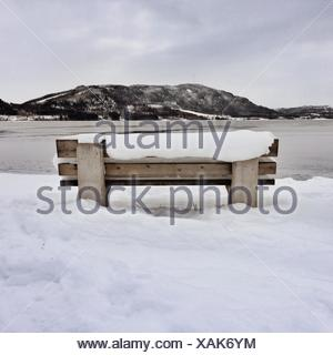 Snow covered bench by fjord, Norway - Stock Photo