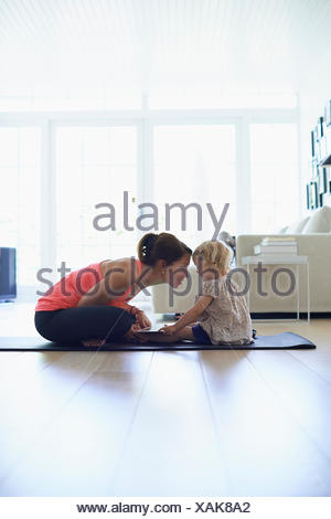 Mid adult mother and toddler daughter practicing lotus position in living room - Stock Photo