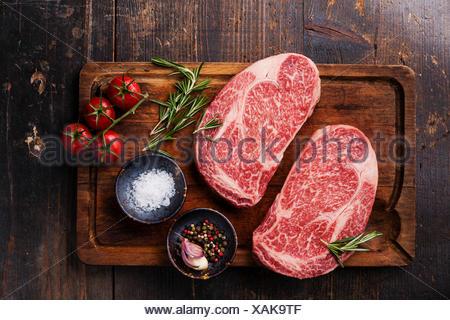 Two Raw fresh marbled meat Black Angus Steak Ribeye and seasonings on dark wooden background - Stock Photo