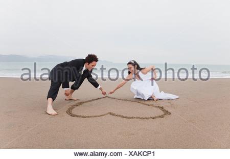 USA, California, San Francisco, Baker Beach, bride and groom drawing heart in sand on beach - Stock Photo