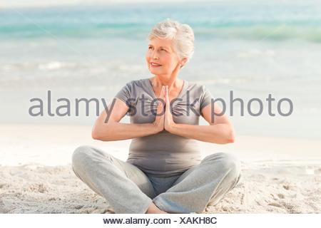 Senior woman practicing yoga on the beach - Stock Photo