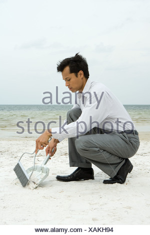 Man crouching on beach using broom and dustpan - Stock Photo