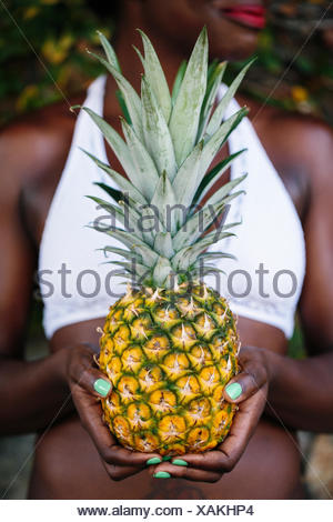 A Caribbean woman holding a fresh pineapple in her hand. - Stock Photo