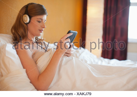 Netherlands, Goirle, Young pregnant woman listening to music in bed - Stock Photo